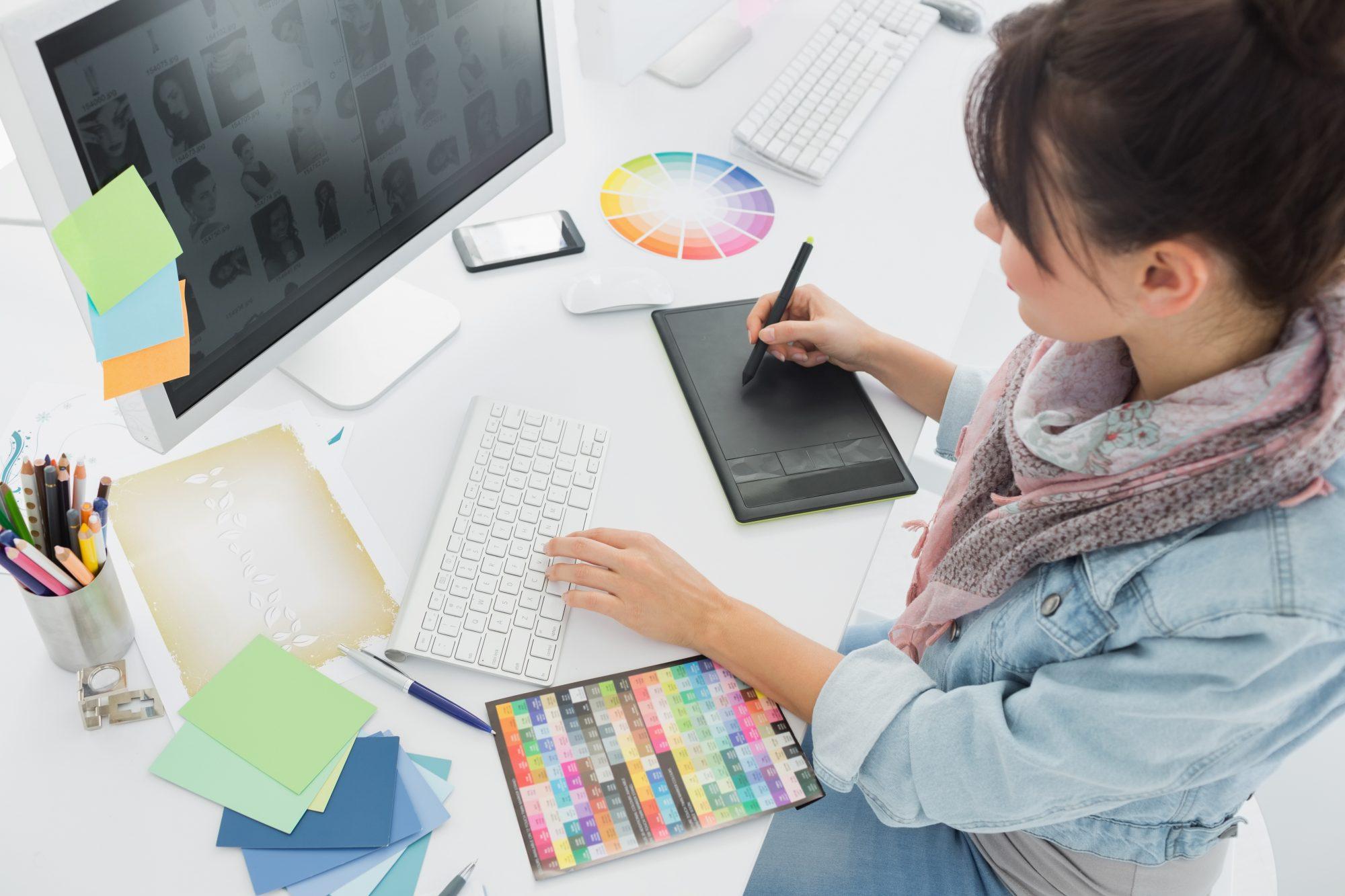 Grafikerin mit Farbfächer am PC