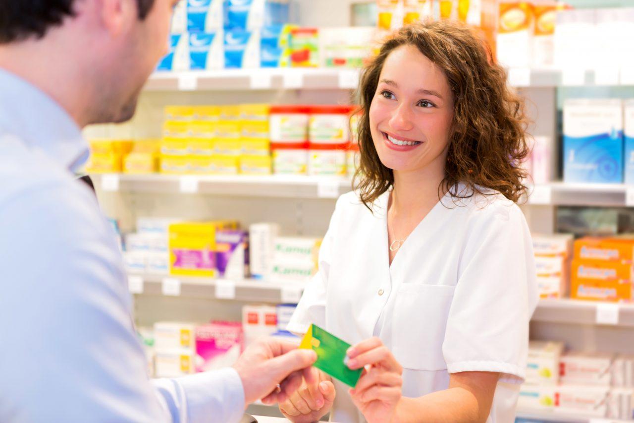 Apothekerin nimmt Kundenkarte entgegen